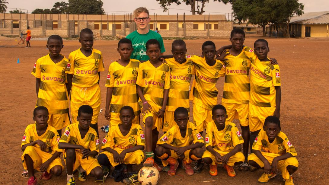Un entraîneur de football de Projects Abroad pris en photo avec ses joueurs au Ghana.
